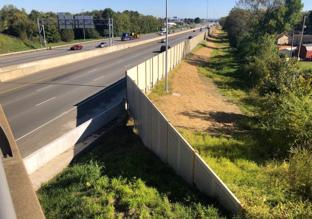 Overpass view of highway noise barrier wall